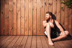 Handsome young bearded man sitting and looking away Royalty Free Stock Image