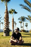 Handsome young bearded man in sunglasses sitting on the grass under palms on summer vocation luxary resort. Handsome bearded man in sunglasses sitting on the Stock Images