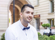 Handsome young bearded man with white shirt and bow tie on the street Royalty Free Stock Photography