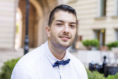 Handsome young bearded man with white shirt and bow tie on the street Stock Photo