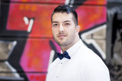 Handsome young bearded man with white shirt and bow tie on the street Stock Photos