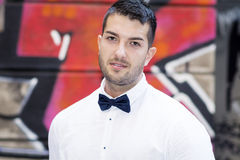 Handsome young bearded man with white shirt and bow tie on the street. Handsome young bearded man with white shirt and tie smiling on a graffiti wall Royalty Free Stock Photo