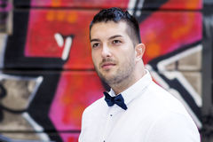 Handsome young bearded man with white shirt and bow tie on the street Stock Image
