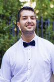 Handsome young bearded man with white shirt and bow tie on the street Stock Photography