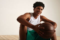 Handsome young black basketball player sitting on the wooden floor Stock Photos