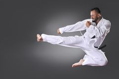 Handsome young black belt male karate doing kick Stock Photography