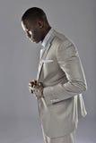 Black man in a suit adjust his coat Stock Photo
