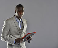 Black man in a suit holding tablet computer Royalty Free Stock Photography