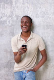 Handsome young black guy laughing with mobile phone. Portrait of handsome young black guy laughing with mobile phone Royalty Free Stock Photo