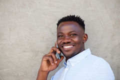 Handsome young black man making a phone call by wall Stock Photos