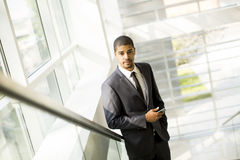 Handsome young black man with mobile phone in the office Stock Photos