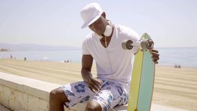 Handsome young black man seated on beach wall