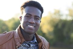 Handsome young black man smiling with defocused trees in the bac Stock Images