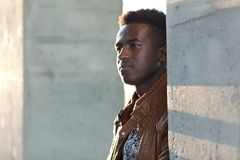 Handsome young black man stands between concrete pillars Royalty Free Stock Photos