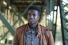 Handsome young black man stands among girders of a bridge. Selective focus image of a handsome young black man standing below girders of a bridge Royalty Free Stock Photography