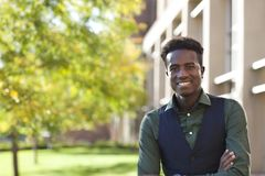 Handsome young black student man smiles standing on colege campu Royalty Free Stock Photo