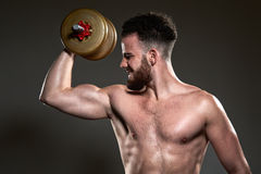 Handsome young body builder using bar bell, on grey background Stock Images