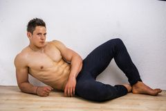 Handsome young bodybuilder laying down on the Stock Image