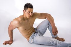 Handsome young bodybuilder laying down on the Stock Images