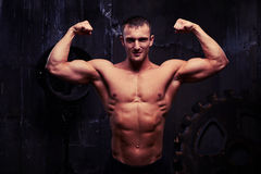 Handsome young bodybuilder posing shirtless in dim light of the Stock Photography
