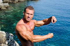 Handsome young bodybuilder by the sea showing arms Royalty Free Stock Photography