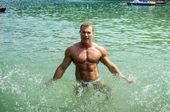 Handsome young bodybuilder in the sea, splashing water up Royalty Free Stock Photo