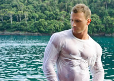 Handsome young bodybuilder by the sea with wet shirt on Royalty Free Stock Photography