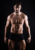 Handsome young bodybuilder showing of his fit body. And muscles Royalty Free Stock Photos