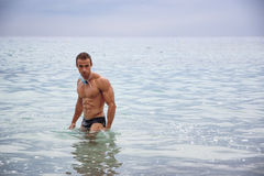 Handsome young bodybuilder and swimmer in the sea Stock Photo