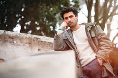 Handsome young bored man leaning on a wall. Outdoor Royalty Free Stock Photos