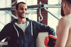 Handsome young boxers. Handsome young muscular boxers are talking and smiling while training at the fight club Royalty Free Stock Photos