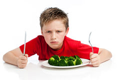 Handsome Young Boy Eating Broccoli. Grumpy young boy with plate of broccoli.  on white background Royalty Free Stock Image