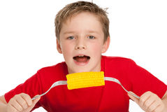 Handsome Young Boy Eating Corn on the Cob. Healthy young boy eating a corn on the cob. Isolated on a white background Royalty Free Stock Photo