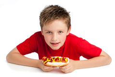 Handsome Young Boy Eating a Hotdog. Good looking young boy eating a hoydog with tomato ketchup and mustard.  on white background Royalty Free Stock Images