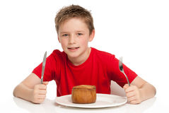 Handsome Young Boy Eating Pork Pie. Young boy eating a tasty pork pie with a knife and fork.  on a white background Royalty Free Stock Photography