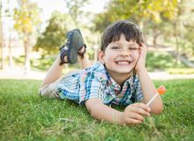 Handsome Young Boy Enjoying His Lollipop Outdoors on the Grass. royalty free stock photography