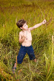 Handsome young boy having fun playing on the meadow in summer wi Stock Photography