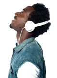 A handsome young boy with headphones. A handsome young boy listening to music on his mp3 player, looking up Royalty Free Stock Image