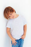 Handsome young boy, kid posing near the white wall royalty free stock image