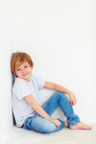 Handsome young boy, kid posing near the white wall stock photography