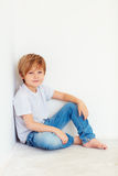 Handsome young boy, kid sitting near the white wall stock images
