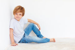 Handsome young boy, kid sitting near the white wall royalty free stock photos