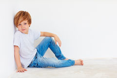 Handsome young boy, kid sitting near the white wall stock photo