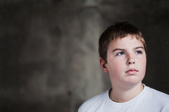 Handsome Young boy looking up with determination. Young handsome boy looking up with determination in his eyes against grunge background flash lit 3 light stock photos