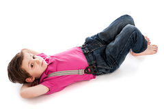 Handsome Young Boy Lying Down. Trendy young toddler boy, lying down on studio white background. Looking to camera with his hands behind his head. Isolated on a Royalty Free Stock Images
