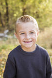 Handsome Young Boy Portrait. A cute, smiling, young boy portrait outdoors. Toothless grin with his front teeth missing stock photography