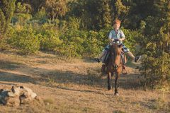 Handsome Young boy with red hair and blue eyes playing with his friend horse pony in forest.Huge love between kid shild and animal Royalty Free Stock Photo