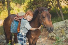 Handsome Young boy with red hair and blue eyes playing with his friend horse pony in forest.Huge love between kid shild and animal. Pet farm Stock Images