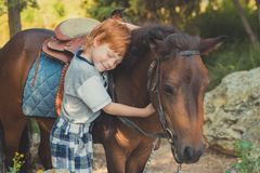 Handsome Young boy with red hair and blue eyes playing with his friend horse pony in forest.Huge love between kid shild and animal. Pet farm Stock Photography