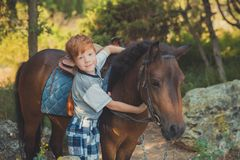 Handsome Young boy with red hair and blue eyes playing with his friend horse pony in forest.Huge love between kid shild and animal. Pet farm Stock Photos